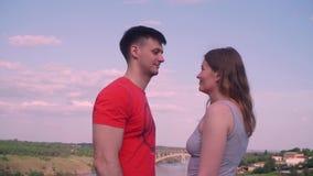 Chłopiec, dziewczyna iść spotykać each inny i spojrzenie, ono uśmiecha się w jego oczach przeciw niebu, most, natura zbiory