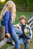 Chłopiec dziewczyna na płotowy patrzeć i ono uśmiecha się Zdjęcia Stock