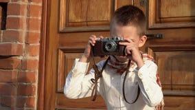 Chłopiec fotografie na retro kamera w retro odziewają przeciw tłu ceglany dom zdjęcie wideo