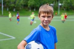 Chłopiec futbolista z piłką na boisko do piłki nożnej Fotografia Royalty Free