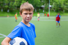 Chłopiec futbolista z piłką w stadium fotografia stock