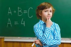 Chłopiec główkowanie na blackboard tle Edukacyjny i szkolny pojęcie obrazy royalty free