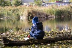 Chłopiec główkowanie na jeziorze w miasto parku fotografia stock