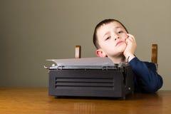 Chłopiec główkowanie przed starym maszyna do pisania obraz royalty free