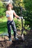 Chłopiec głębienie po dżdżownic w ogródzie Zdjęcia Royalty Free