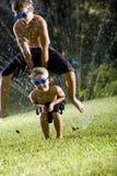 chłopiec gazonu leapfrog nad bawić się kropidło obraz stock
