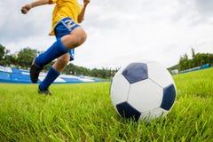 Chłopiec gracz futbolu uderza piłkę Zdjęcie Royalty Free