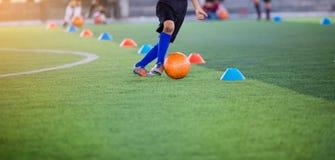 Chłopiec gracz piłki nożnej kontroli i oklepa futbol między szyszkowymi producentami obrazy stock