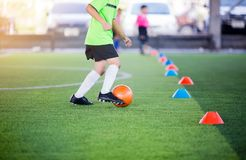 Chłopiec gracz piłki nożnej kontroli i oklepa futbol między szyszkowymi producentami zdjęcie royalty free