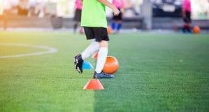 Chłopiec gracz piłki nożnej kontroli i oklepa futbol między szyszkowymi producentami zdjęcia royalty free