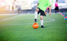 Chłopiec gracz piłki nożnej kontroli i oklepa futbol między szyszkowymi producentami obrazy royalty free