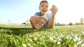 Chłopiec gracz piłki nożnej sporta napojów woda od plastikowej butelki między sesjami szkoleniowymi nastoletnia chłopiec bawić si zbiory