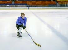 Chłopiec gracz w hokeja z pełnym wyposażeniem pozuje z hocke Obrazy Royalty Free