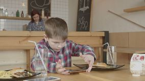 Chłopiec hazard na telefonie podczas gdy jedzący w kawiarni zbiory