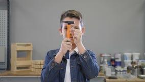 Chłopiec i budynku narzędzia z młotem i gwoździe w rękach zamyka oczu ono uśmiecha się i otwiera Handcraft pojęcie hobby zbiory wideo