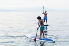 Chłopiec i daleki ćwiczyć stoimy up paddles obrazy royalty free