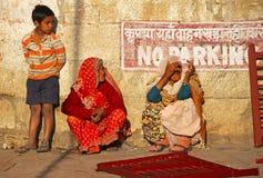 Chłopiec i Dwa starszych osob Indiańska kobieta siedzimy w drzwi dom zdjęcia stock