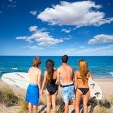 Chłopiec i dziewczyn surfingowów tylni widoku nastoletnia przyglądająca plaża Zdjęcia Royalty Free