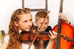 Chłopiec i dziewczyna bawić się instrumenty muzycznych wpólnie Zdjęcia Royalty Free