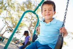Chłopiec I dziewczyna Bawić się Na huśtawce W parku Zdjęcia Stock