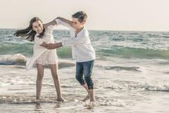 Chłopiec i dziewczyna bawić się na seashore obraz stock