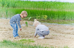 Chłopiec i dziewczyna bawić się w piasku na brzeg jezioro Zdjęcie Royalty Free