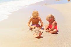 Chłopiec i dziewczyna bawić się z wodą na plaży Obrazy Royalty Free