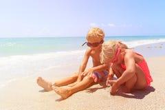 Chłopiec i dziewczyna bawić się z wodą na plaży Obraz Royalty Free