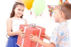 Chłopiec i dziewczyna daje teraźniejszości each inny Obrazy Stock