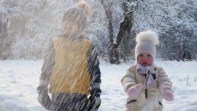 Chłopiec i dziewczyna ogląda śnieg spadać od drzewa zbiory wideo