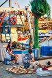 Chłopiec i dziewczyna opowiada na molu na tle połowu trawler Obraz Stock