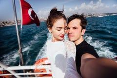 Chłopiec i dziewczyna, para Robi selfie na pokładzie łódkowatego rejsu być na wakacjach Przeciw tłu Turecka flaga morze i Zdjęcia Royalty Free