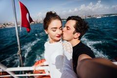 Chłopiec i dziewczyna, para Robi selfie na pokładzie łódkowatego rejsu być na wakacjach Przeciw tłu Turecka flaga morze i Zdjęcie Stock
