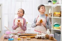 Chłopiec i dziewczyna pokazujemy piec ciastka, domowy kuchenny wnętrze, domowej roboty karmowy pojęcie Obraz Royalty Free