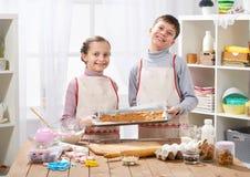 Chłopiec i dziewczyna pokazujemy tacę piec ciastka, domowy kuchenny wnętrze, domowej roboty karmowy pojęcie Obraz Royalty Free
