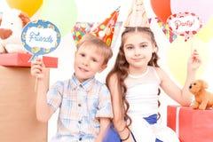 Chłopiec i dziewczyna pozuje podczas przyjęcia urodzinowego Obraz Stock