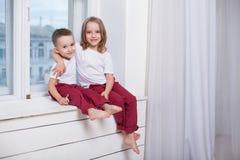 Chłopiec i dziewczyna siedzimy na windowsill przyglądającym za okno obraz royalty free
