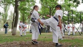 Chłopiec i dziewczyna w kimonie trenuje w parku uczestniczymy pojedynczą walkę, karate outdoors, sztuki samoobrony, sporty dla dz zbiory wideo