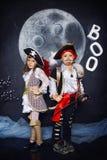 Chłopiec i dziewczyna w piratów kostiumach pojęcie kalendarzowej daty Halloween gospodarstwa ponury miniatury szczęśliwa reaper,  Zdjęcia Stock
