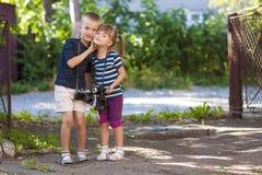 Chłopiec i dziewczyny dowcipu dwa rocznika kamery stoi troszkę Obraz Stock