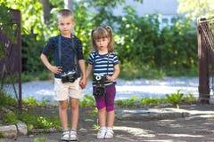 Chłopiec i dziewczyny dowcipu dwa rocznika kamery stoi troszkę Fotografia Royalty Free