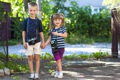 Chłopiec i dziewczyny dowcipu dwa rocznika kamery stoi troszkę Fotografia Stock