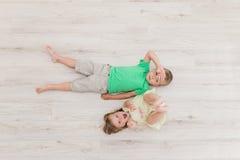 Chłopiec i dziewczyny lying on the beach na podłoga Fotografia Stock