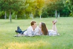 Chłopiec i dziewczyny lying on the beach na trawie patrzeje each zdjęcia stock