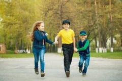 Chłopiec i dziewczyny mienia bieg w parku i ręki Obrazy Stock