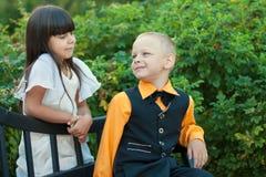 Chłopiec i dziewczyny obsiadanie na ławce blisko drzew Zdjęcia Stock