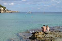 Chłopiec i dziewczyny obsiadanie na skale Cala Ważna plaża w Palmie de Mallorca, Hiszpania obrazy stock