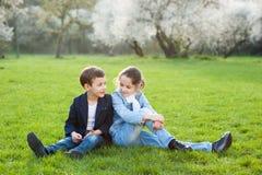 Chłopiec i dziewczyny obsiadanie na zielonej łące fotografia stock