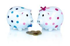 Chłopiec i dziewczyny prosiątka bank dla save pieniądze z euro monetami na białym tle z cienia odbiciem obraz stock
