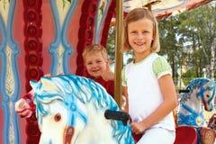 Chłopiec i dziewczyny przejażdżka na carousel Zdjęcia Royalty Free